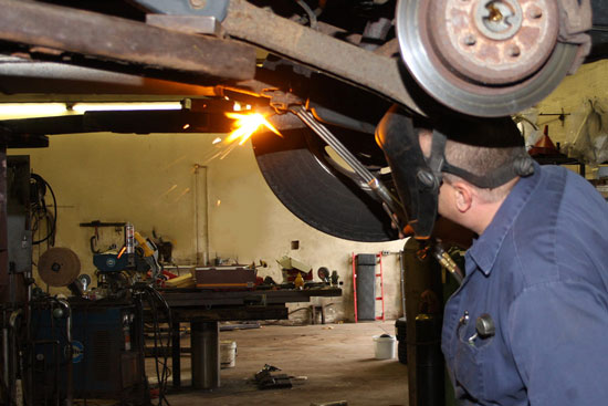 Mechanic welding an exhaust system